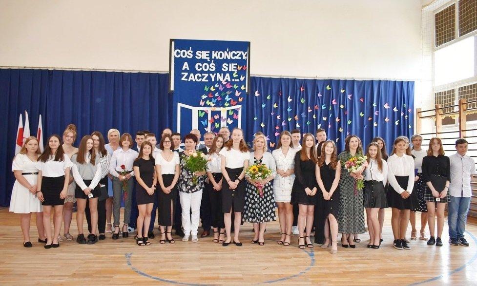 Zdjęcie przedstawia ósmoklasistów, wychowawców, dyrekcję, władze gminy, Księdza Proboszcza podczas zakończenia roku w Publicznej Szkole Podstawowej w Rusinowie
