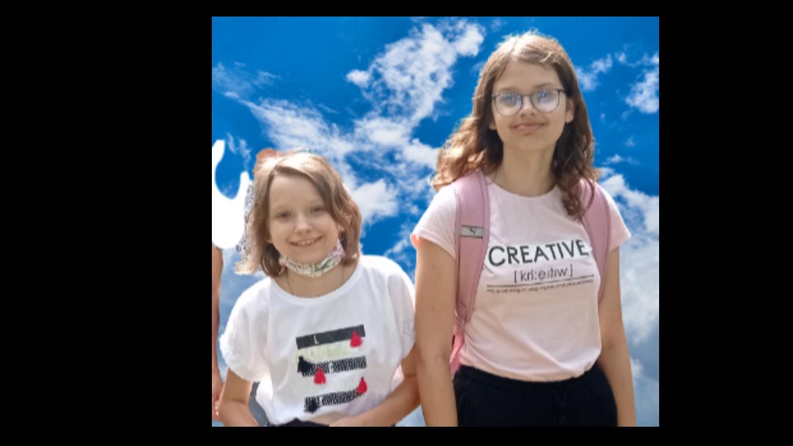 Zdjęcie przedstawia uczennice PSP Roksanę Papis oraz Gabrielę Kokosińską. Dziewczynki znajdują się na głównym planie. Tło niebieskie z chmurami.