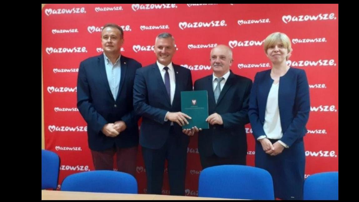 Zdjęcie przedstawia władze samorządowe Gminy Rusinów oraz UMWM. Czerwone tło z logo mazowsza. Niebieskie krzesła. Trzech mężczyzn i kobieta.