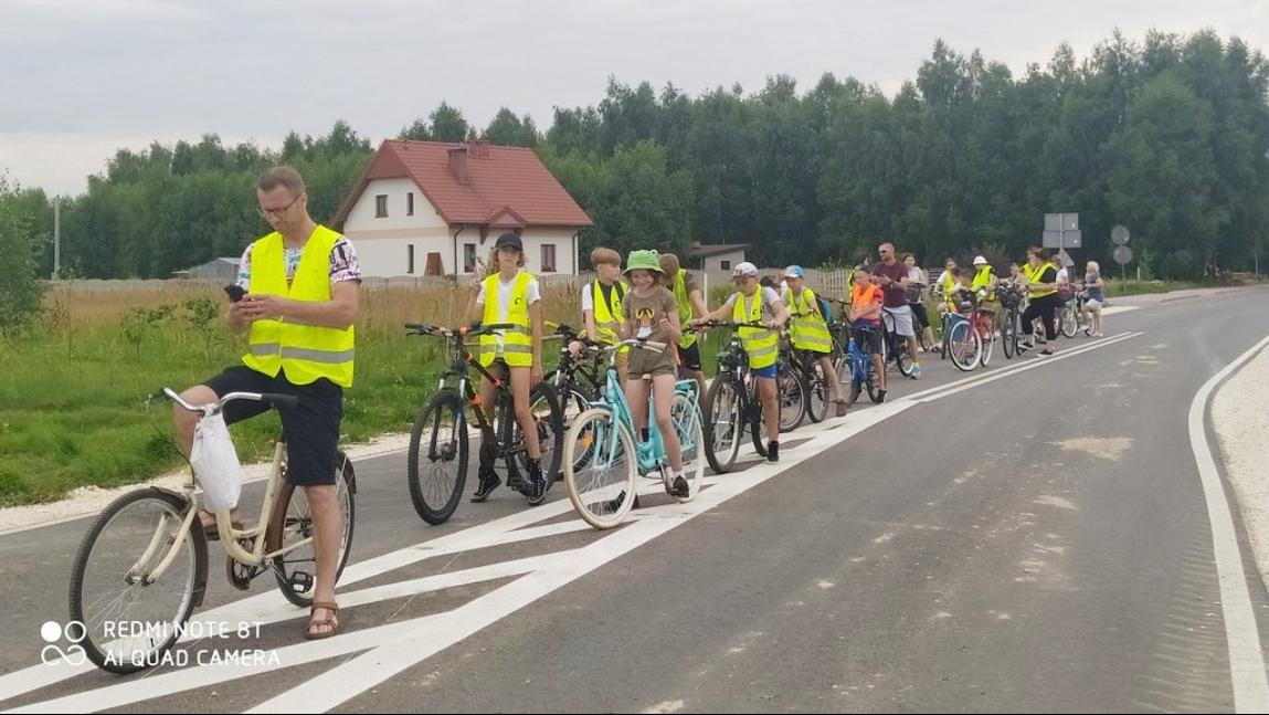 zdjęcie przedstawia grupę dzieci wraz z opiekunami na rowerach. Znajdują się na jezdni. w tle pola, dom z czerwonym  dachem oraz las. Góra zdjęcia - niebo.